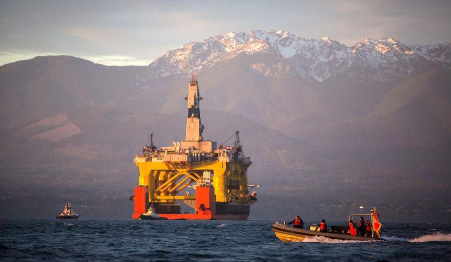 FILE - In this April 17, 2015, file photo, with the Olympic Mountains in the background, a small boat crosses in front of an oil drilling rig as it arrives in Port Angeles, Wash., aboard a transport ship after traveling across the Pacific. Royal Dutch Shell hopes to use the rig for exploratory drilling during the summer open-water season in the Chukchi Sea off Alaska's northwest coast, if it can get the permits. (Daniella Beccaria/seattlepi.com via AP, File) MAGS OUT; NO SALES; SEATTLE TIMES OUT; TV OUT; MANDATORY CREDIT