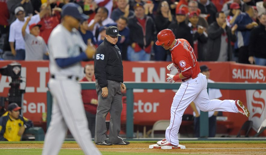 Los Angeles Angels' Mike Trout, right, rounds third as Seattle Mariners starting pitcher Roenis Elias walks off the mound as third base umpire Greg Gibson watches during the third inning of a baseball game, Wednesday, May 6, 2015, in Anaheim, Calif. (AP Photo/Mark J. Terrill)