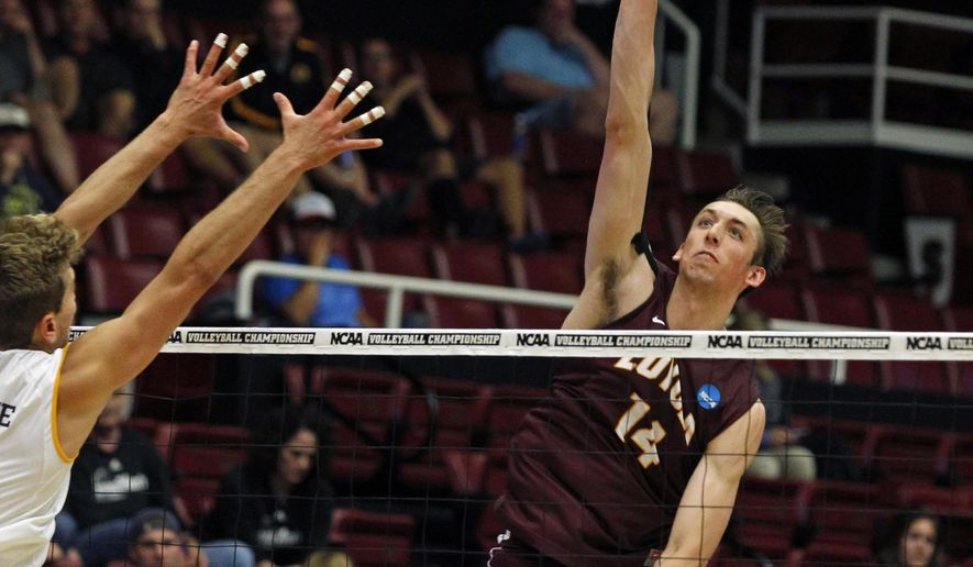 Loyola Chicago's Ricky Gevis hits the ball as UC Irvine's Travis Woloson defends during an NCAA Division I volleyball semifinal match, Thursday, May 7, 2015, in Stanford, Calif. (AP Photo/George Nikitin)