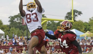 Washington Redskins tight end Fred Davis (83) grabs a pass in front of strong safety DeJon Gomes (24) during afternoon practice at NFL football training camp in Richmond, Va., Tuesday, July 30, 2013. (AP Photo/Steve Helber)