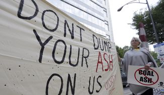 Debbie Hall, of Sanford, N.C., holds a sign protesting coal ash ponds, outside the Duke Energy headquarters before the company's shareholders meeting in Charlotte, N.C., Thursday, May 7, 2015. (AP Photo/Chuck Burton)