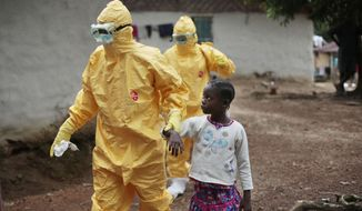 Nowa Paye, 9, is taken to an ambulance after showing signs of the Ebola infection in the village of Freeman Reserve, Liberia, on Sept. 30, 2014. (Associated Press)