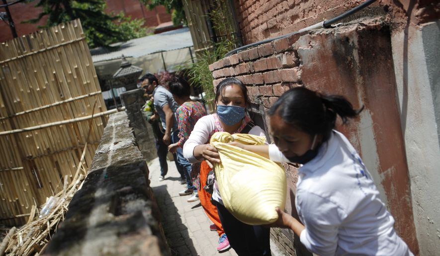In this Tuesday, May 5, 2015, photo, Nepalese volunteers form a chain to load food and relief material collected by two Portuguese men onto a vehicle, for distribution among the earthquake affected in Kathmandu, Nepal. (AP Photo/Niranjan Shrestha)