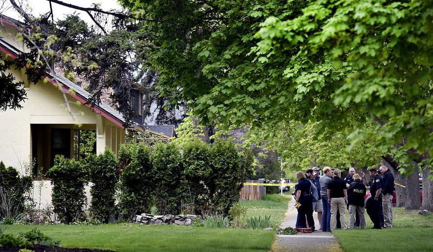 In this May 6, 2015, photo, Missoula Police investigators gather outside a home shortly after they responded to reports of gunshots at the home and found two people fatally wounded in Missoula, Mont. The news director of a southwestern Montana television station was killed along with a family friend in a double murder-attempted suicide at her residence, KTMF station manager Tom Ciprari said Thursday. (Kurt Wilson/The Missoulian via AP)