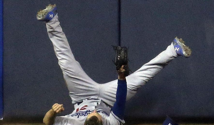 Los Angeles Dodgers center fielder Joc Pederson runs into the wall after catching a ball hit by Milwaukee Brewers' Wily Peralta during the sixth inning of a baseball game Wednesday, May 6, 2015, in Milwaukee. (AP Photo/Morry Gash)