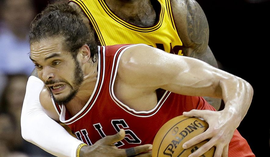 Cleveland Cavaliers forward LeBron James (23) tries to knock the ball loose from Chicago Bulls center Joakim Noah (13) during the second half of Game 2 in a second-round NBA basketball playoff series Wednesday, May 6, 2015, in Cleveland. (AP Photo/Tony Dejak)