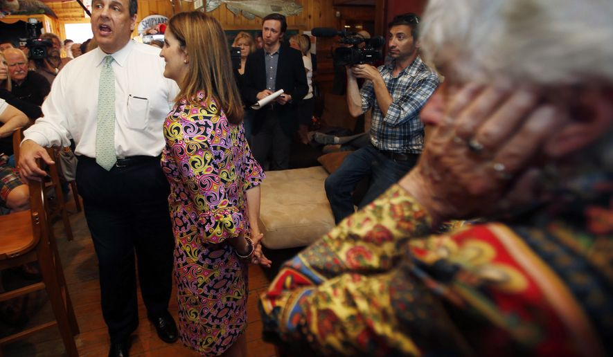 Barbara McGuiness, right, listens as possible 2016 presidential candidate Republican New Jersey Gov. Chris Christie speaks at the One Mile West restaurant Thursday, May 7, 2015, in Sunapee, N.H. (AP Photo/Jim Cole)