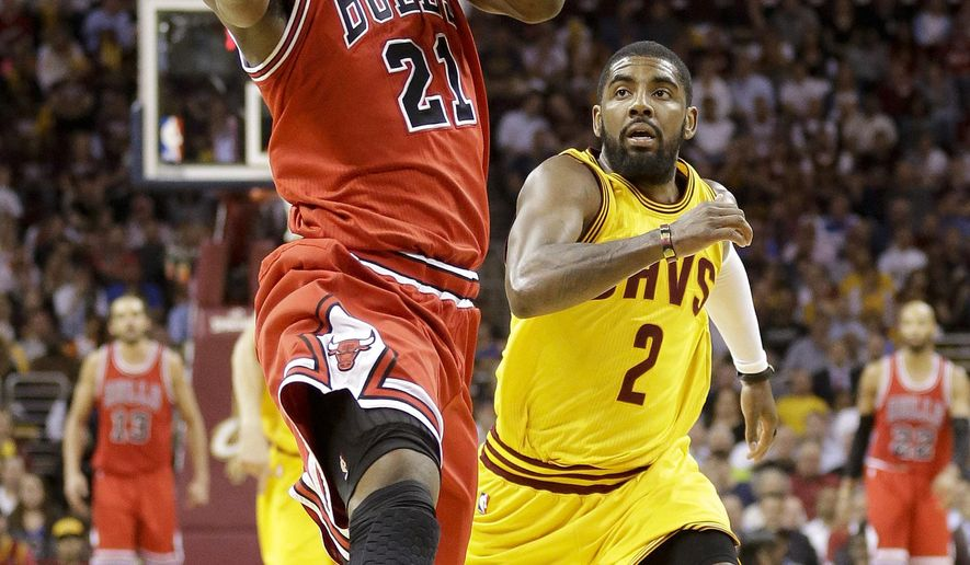 Chicago Bulls guard Jimmy Butler (21) drives to the lane against Cleveland Cavaliers guard Kyrie Irving (2) during the first half of Game 2 in a second-round NBA basketball playoff series Wednesday, May 6, 2015, in Cleveland. The Cavaliers won 106-91. (AP Photo/Tony Dejak)