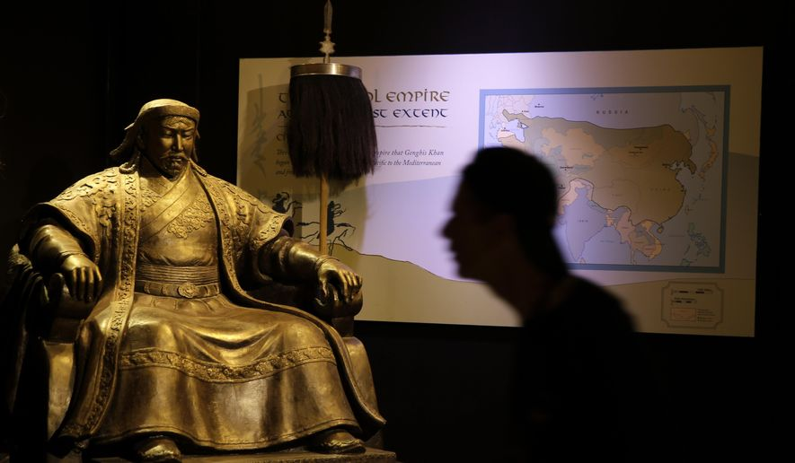 A photographer walks past a statue of Genghis Khan at the Genghis Khan: Bring the Legend to Life exhibit during a press preview, Thursday, May 7, 2015, at the The Franklin Institute in Philadelphia.  The exhibition uses 13th-century weapons, jewels and religious relics to tell the story of the renowned Mongolian conqueror and is scheduled to open to the public on Saturday. (AP Photo/Matt Slocum)