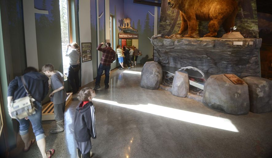 Visitors browse the new Kenai Wildlife Refuge Visitors Center Friday, May 1 at the Kenai Wildlife Refuge Headquarters in Soldotna, Alaska. Kenai Refuge staff said their new visitor center, which began construction in 2013 and opened to the public for the first time on May 1, 2015, is not only larger than their previous center but more interactive.  (Ben Boettger/Peninsula Clarion via AP) MANDATORY CREDIT