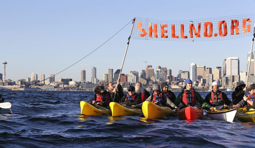 In this photo taken on April 16, 2015, a group of kayakers rafted together work to pull up a protest sign as they practice for an upcoming demonstration against Arctic oil drilling, in Elliott Bay in view of downtown Seattle. (AP Photo/Elaine Thompson)