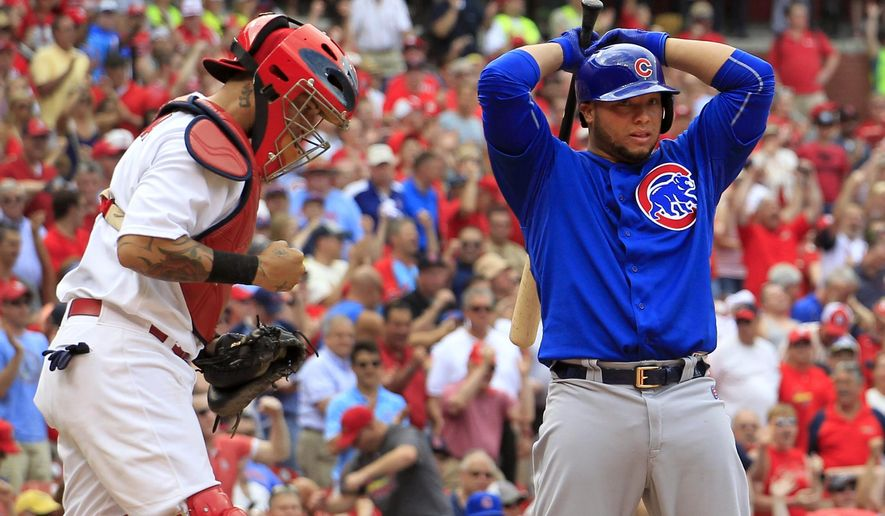 St. Louis Cardinals catcher Yadier Molina, left, pumps his fist as Chicago Cubs' Welington Castillo stands at the plate after Castillo was called out on strikes to end a baseball game Thursday, May 7, 2015, in St. Louis. The Cardinals won 5-1. (AP Photo/Jeff Roberson)