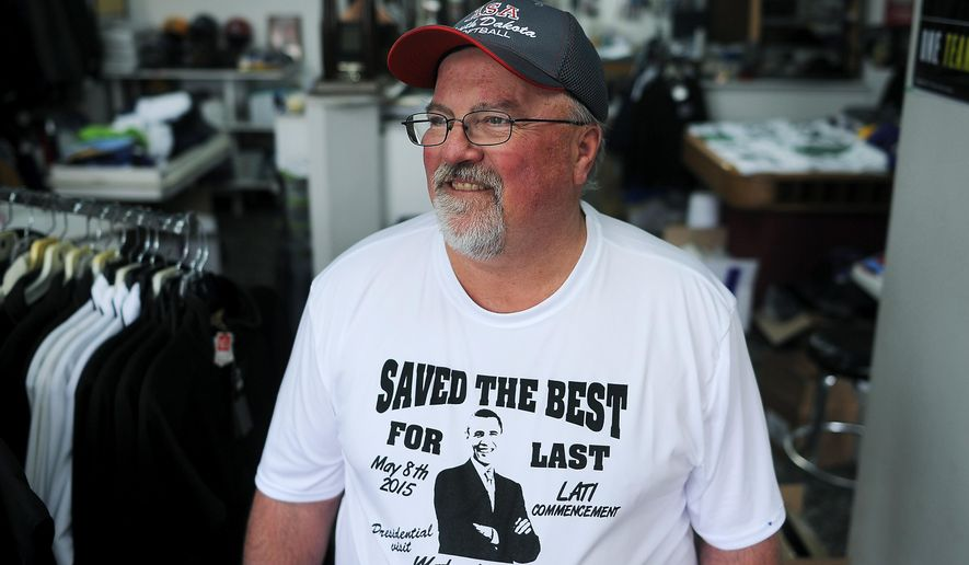 "Gary Young, owner of Young's Primtime Sports, in Watertown, S.D., poses for a portrait in a ""Saved the Best for Last"" t-shirt he made on Wednesday, May 6, 2015, ahead of President Barack Obama's visit on Friday.  Obama checks the 50th state off his list of places to visit with a planned commencement speech Friday in Watertown before about 600 tech school grads and their families.  (Joe Ahlquist/The Argus Leader via AP) NO SALES"
