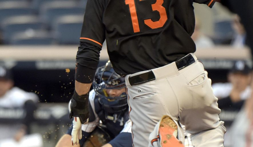 New York Yankees catcher Brian McCann, left, fields the throw as Baltimore Orioles' Manny Machado attempts to score on a single by Delmon Young during the first inning of a baseball game Friday, May 8, 2015, at Yankee Stadium in New York. Machado was tagged out on the play. (AP Photo/Bill Kostroun)