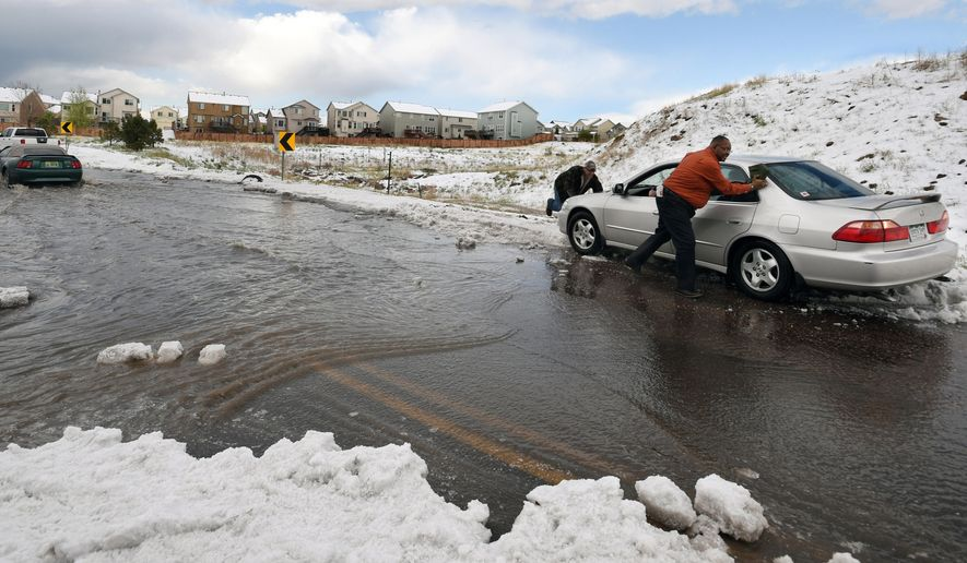 FILE - In this May 7, 2015 file photo, Robert Barnes, right, and Scott Riggs, left, push a stranded motorist out of a drift of hail in Colorado Springs, Colo. A storm system sweeping across the state brought heavy rain to much of Colorado's Front Range, including up to 8 inches of hail in Colorado Springs. (Jerilee Bennett/The Gazette via AP, File)