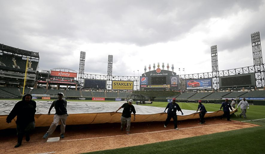 The grounds crew at US Cellular Field pulls on the rain tarp as thunderstorms come through the area before an interleague baseball game between the Chicago White Sox and the Cincinnati Reds in Chicago, Friday, May 8, 2015. (AP Photo/Jeff Haynes)