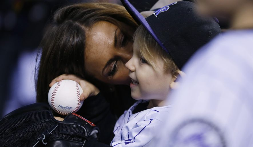 Nicole Axford, back, kisses her 2-year-old son, Jameson, as he waits to throw out the ceremonial first pitch before the Colorado Rockies host the Los Angeles Dodgers in a baseball game Friday, May 8, 2015, in Denver. The little boy, who is the son of Rockies relief pitcher John Axford, is recovering after being bitten by a rattlesnake while with his family in Arizona for spring training. (AP Photo/David Zalubowski)