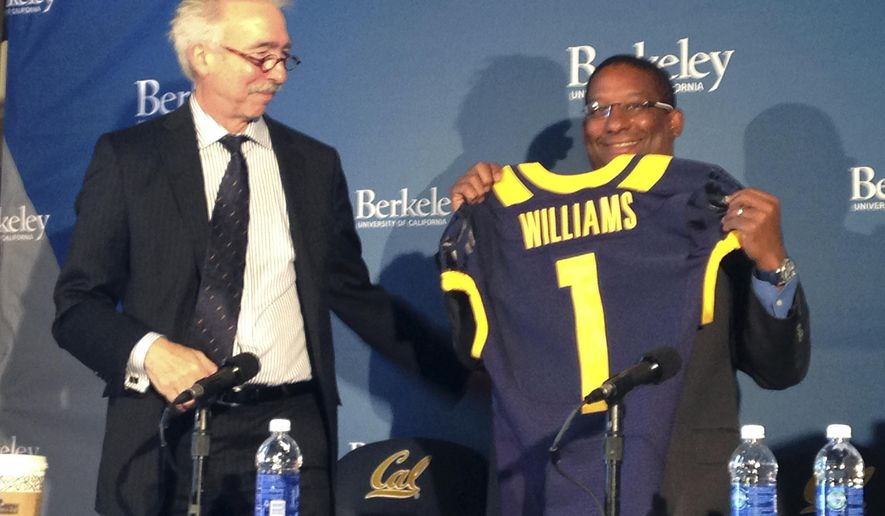 Chancellor Nicholas Dirks, left, presents a jersey to Michael Williams, right, after he was named the athletic director at the University of California, Berkeley Friday, May 8, 2015, in Berkeley, Calif. Williams insisted he didn't want to be California's athletic director when he was appointed to the interim job last summer. Ten months later, the job turned out to be too good to pass up. (AP Photo/Antonio Gonzalez)