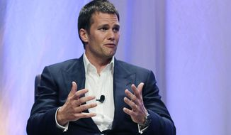 """New England Patriots quarterback Tom Brady gestures during an event at Salem State University in Salem, Mass., Thursday, May 7, 2015. An NFL investigation has found that New England Patriots employees likely deflated footballs and that quarterback Tom Brady was """"at least generally aware"""" of the rules violations. The 243-page report released Wednesday, May 6, 2015, said league investigators found no evidence that coach Bill Belichick and team management knew of the practice. (AP Photo/Charles Krupa, Pool)"""