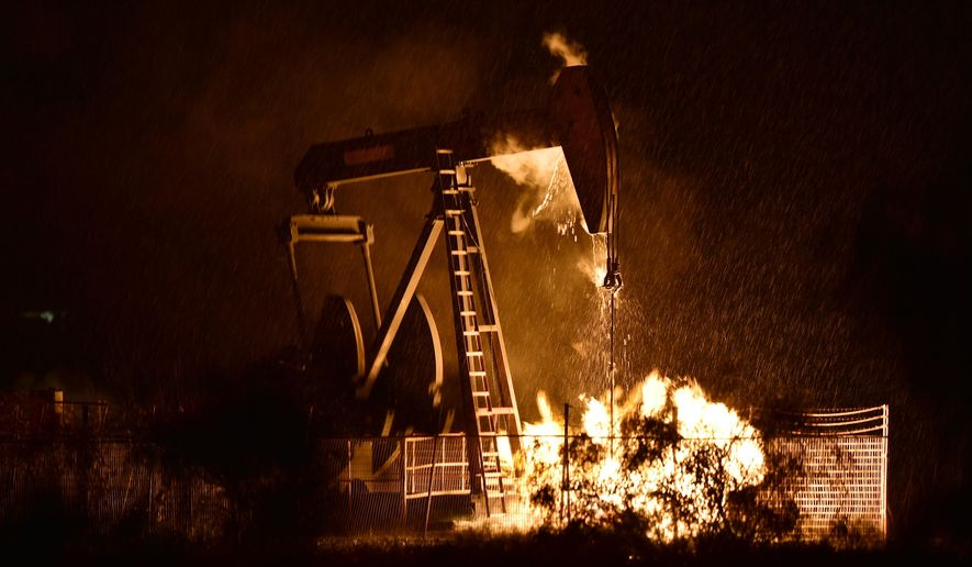 A gas well on the Payne lease, operated by Vantage Energy, burns during a thunderstorm after severe weather and lightning moved across North Texas, Thursday, May 7, 2015, in Denton, Texas. (David Minton/The Denton Record-Chronicle via AP)