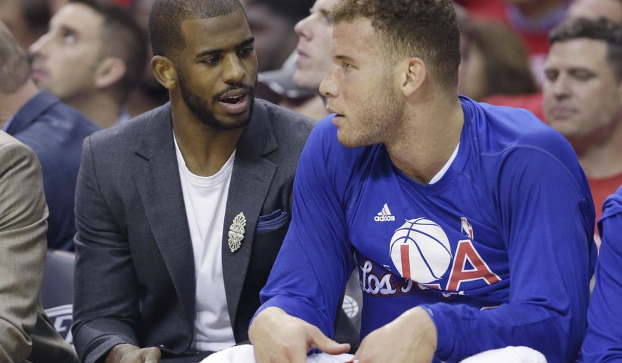 Los Angeles Clippers' Chris Paul, left, and Blake Griffin sit on the bench during the first half of Game 2 in a second-round NBA basketball playoff series against the Houston Rockets, Wednesday, May 6, 2015, in Houston. Paul is out for Game 2 with a strained left hamstring. (AP Photo/David J. Phillip)