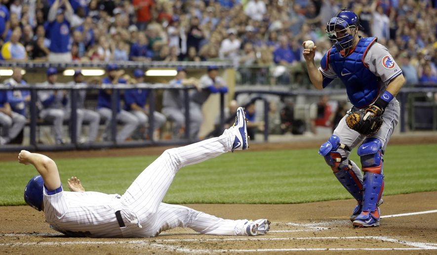Chicago Cubs catcher Miguel Montero, right, shows the ball after tagging out Milwaukee Brewers' Adam Lind at home during the first inning of a baseball game Friday, May 8, 2015, in Milwaukee. Lind tried to score from second on a hit by Gerardo Parra. (AP Photo/Morry Gash)