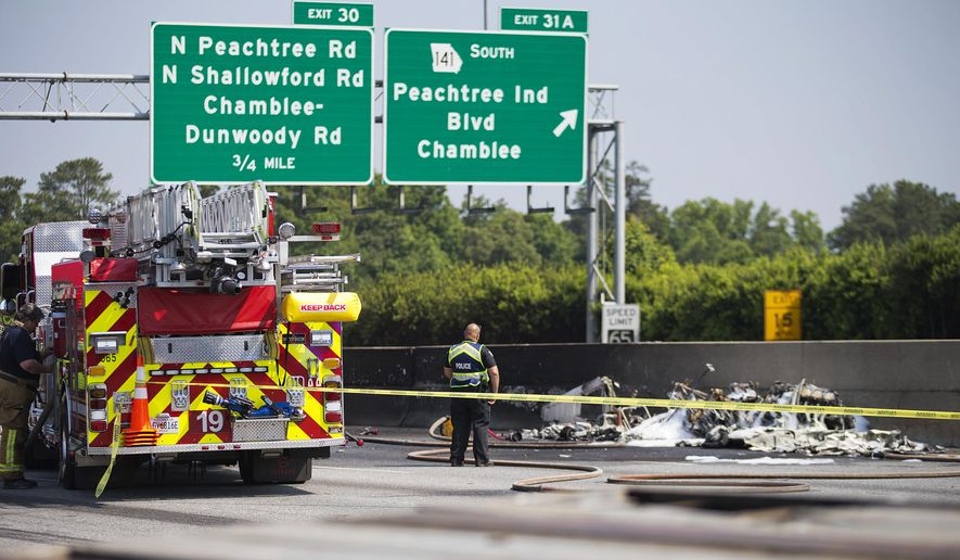 A police officer looks at the wreckage of a plane that crashed on Interstate 285, Friday, May 8, 2015, in Doraville, Ga. A small passenger airplane crashed into an Atlanta interstate Friday, killing all four people aboard and starting an intense fire on the busy road, authorities said. (AP Photo/David Goldman)
