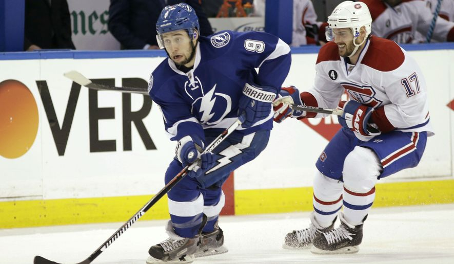 Tampa Bay Lightning center Tyler Johnson, left, and Montreal Canadiens center Torrey Mitchell, right, battle for the puck during second period of Game 4 NHL second round playoff hockey action, Thursday, May 7, 2015, in Tampa, Fla. The Canadiens defeated the Lightning 6-2. (AP Photo/Wilfredo Lee)