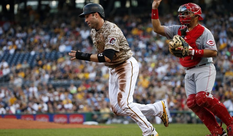 Cincinnati Reds catcher Brayan Pena, right, chases Pittsburgh Pirates' Neil Walker back to third, where he was tagged out by third baseman Todd Frazier, ending a run down between third and home in the first inning of a baseball game Thursday, May 7, 2015, in Pittsburgh. (AP Photo/Gene J. Puskar)