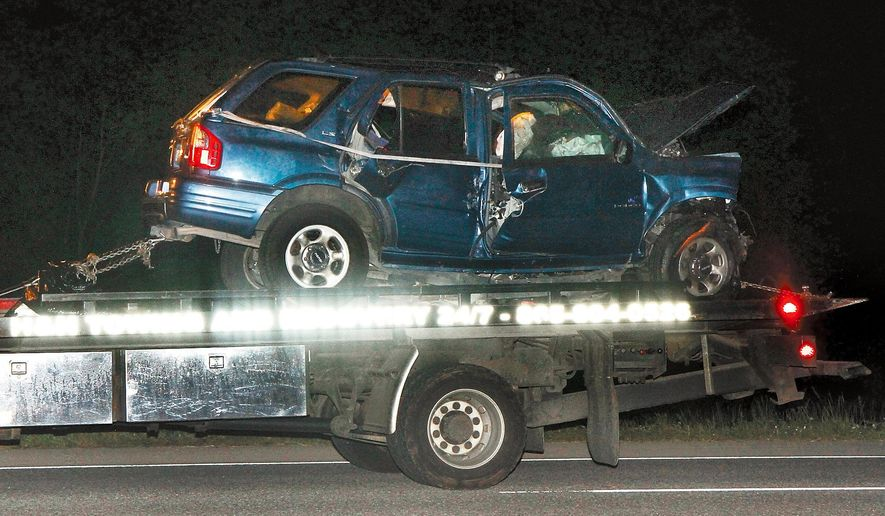 A vehicle is towed away after an accident on U.S. Highway 411 South near Maryville, Tenn., late Thursday, May 7, 2015.  Six people, including three children, have been killed in a crash in eastern Tennessee, the Tennessee Highway Patrol said.  (Daryl Sullivan /The Daily Times via AP)
