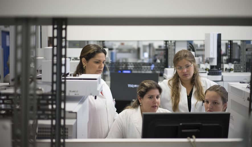Lab technicians work at the Brazilian Doping Control Laboratory (LBCD) before a visit by Brazil's sports minister in Rio de Janeiro, Brazil, Friday, May 8, 2015. The World Anti-Doping Agency (WADA) will decide on May 13 if LBCD is accredited for Biological Passport Analysis. If they are, Brazil will be able to analyze samples for doping control during test events at the 2016 Olympic and Paralympic Games. (AP Photo/Felipe Dana)