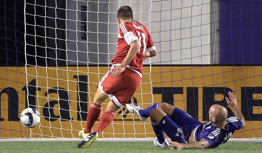 New England Revolution midfielder Kelyn Rowe (11) scores a goal in front of Orlando City defender Aurelien Collin, right, during the second half of an MLS soccer game in Orlando, Fla., Friday, May 8, 2015. The teams tied 2-2. (AP Photo/Phelan M. Ebenhack)
