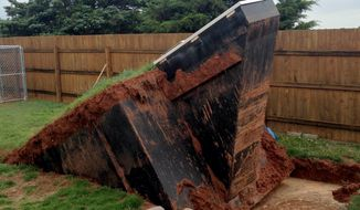 This photo by KOCO shows a storm shelter that came out of the ground after four inches of rain fell Tuesday night, May 5, 2015, through Wednesday morning in Noble, Okla., a surrounding community of Norman. (Morgan Chesky/KOCO via AP)