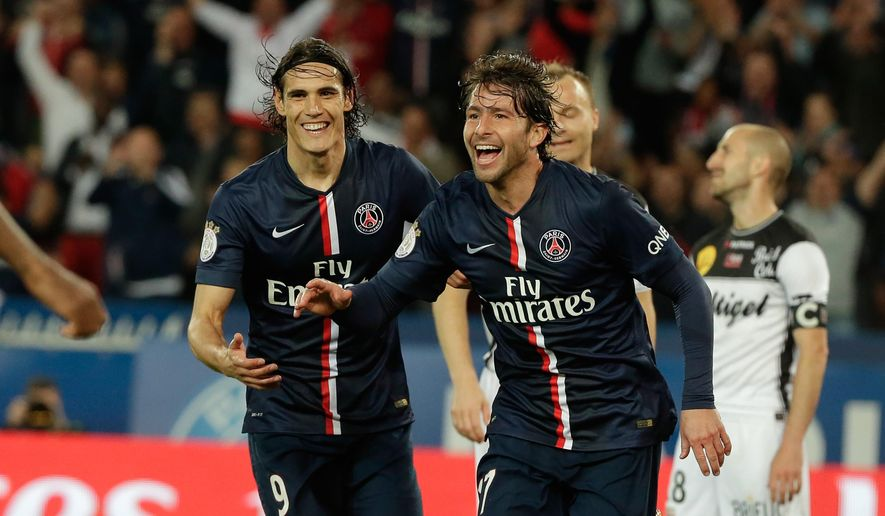 Paris Saint Germain's Maxwell, right, celebrates with teammate Paris Saint Germain's Edinson Cavani after scoring a goal, during his League One soccer match against Guingamp, at the Parc des Princes stadium, in Paris, France, Friday, May 8, 2015. (AP Photo/Thibault Camus)