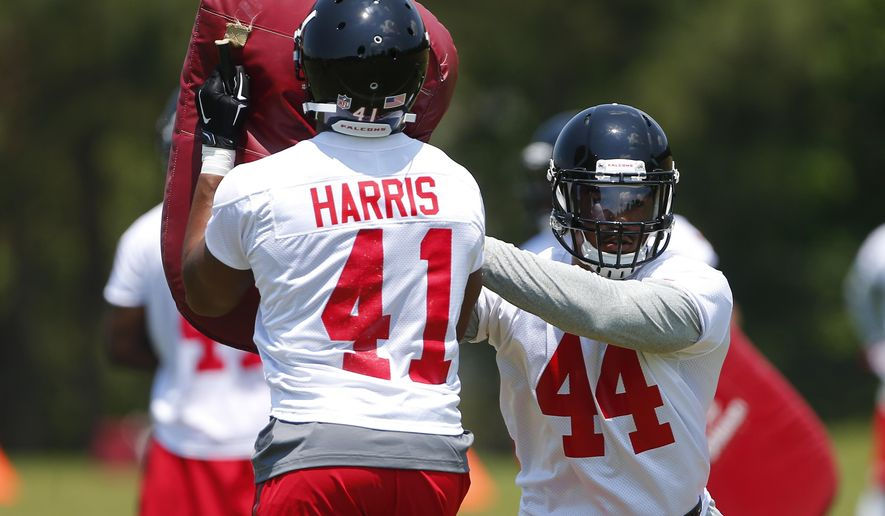 Atlanta Falcons first-round draft pick Vic Beasley (44) works with Charles Harris on a  drill during the first day of NFL rookie minicamp football practice Friday, May 8, 2015, in Flowery Branch, Ga.  (AP Photo/John Bazemore)
