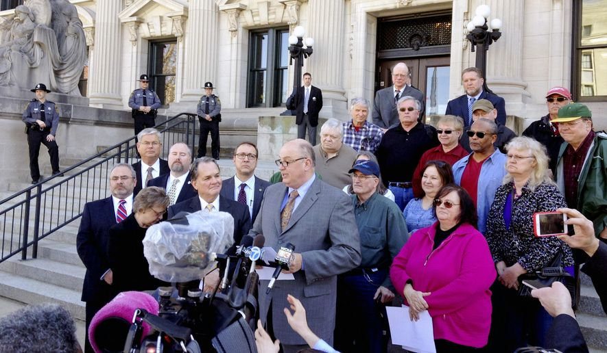 FILE - In this March 11, 2015, file photo, Illinois AFL-CIO President Michael Carrigan is joined by state workers and retirees outside the Illinois Supreme Court in Springfield, Ill., as he addresses the media following oral arguments in a lawsuit over a state pension overhaul. The Illinois Supreme Court on Friday, May 8 struck down a 2013 law that sought to fix the nation's worst government-employee pension crisis, a ruling that forces the state to find another way to overcome a massive budget deficit. (AP Photo/Sara Burnett, File)