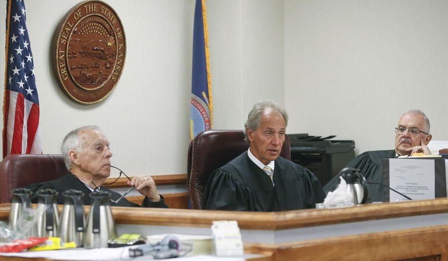 "Labette County District Court Judge Robert Fleming, left, Shawnee County District Court Judge Franklin Theis, center, and former Sherman County District Court Judge Jack Burr, discuss an objection to the plaintiffs exhibit by the state on Friday May 8, 2015 in Topeka, Kan. The Dodge City, Hutchinson, Wichita and Kansas City, Kansas, districts are asking a three-judge panel to block the new school funding law. The new law took effect in April. It scrapped the state's per-pupil formula for distributing aid to public school districts in favor of predictable ""block grants."" (Chris Neal/The Topeka Capital-Journal via AP)"