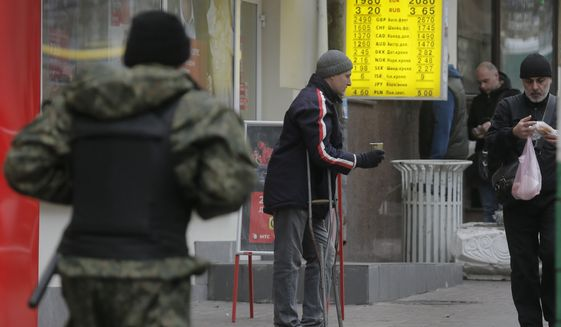 A man begs on a street near a currency exchange bureau in Kiev, Ukraine, Thursday, Nov. 13, 2014.  Ukraine's hryvnia plunged to UAH 15.56/USD on Nov. 13, a 14% decline since Nov. 5, when the National Bank of Ukraine reduced its interventions at the ForEx and allowed further weakening. Ukraine's national currency has already lost nearly 47% of its value this year, falling from UAH 8.1/USD.  (AP Photo/Efrem Lukatsky)