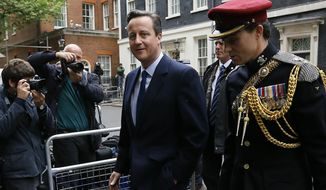 Britain's Prime Minister David Cameron, left, leaves 10 Downing Street in London with a soldier, to attend a VE Day service at the Cenotaph, Friday, May 8, 2015. Cameron's Conservative Party swept to power Friday in Britain's Parliamentary elections winning an unexpected majority.  (AP Photo/Kirsty Wigglesworth)