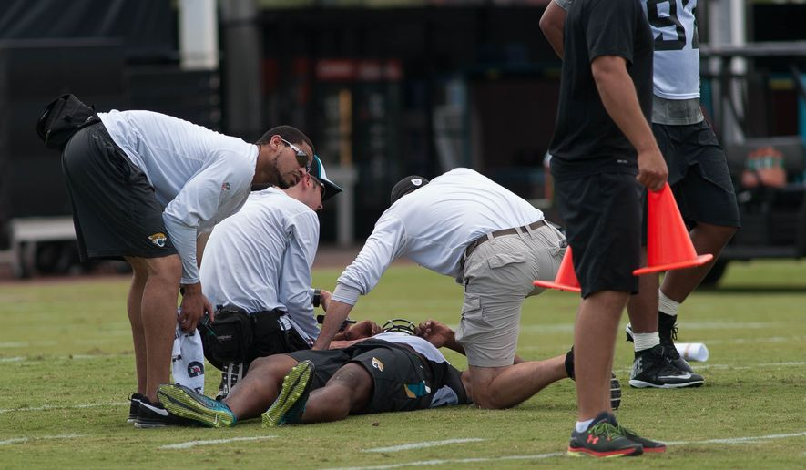 Jacksonville Jaguars first-round draft pick Dante Fowler is tended to after being injured at the teams NFL football minicamp in Jacksonville, Fla., Friday, May 8, 2015. (Fran Ruchalski/The Florida Times-Union via AP)