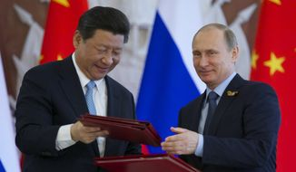Russian President Vladimir Putin, right, and Chinese President Xi Jinping exchange documents at the signing ceremony in the Kremlin in Moscow, Friday, May 8, 2015. Russian and Chinese leaders have signed a plethora of deals in Moscow, giving Russia billions in infrastructure loans. (Associated Press) ** FILE **