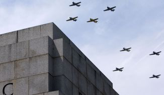 """World War II aircraft fly over the World War II Memorial in Washington, Friday, May 8, 2015, in honor of the 70th anniversary of Victory in Europe Day (VE Day), during the """"Arsenal of Democracy: World War II Victory Capitol Flyover."""" The Flyover above the National Mall features historically sequenced formations of more than 50 vintage World War II aircraft. (AP Photo/Jacquelyn Martin)"""