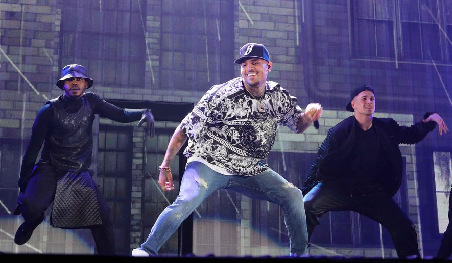 FILE - In this March 2, 2015 file photo, Chris Brown performs during the Between The Sheets Tour at Philips Arena in Atlanta. A woman authorities say broke into the Los Angeles-area home of Brown and spent several days there before he returned has been charged with felony burglary, stalking and vandalism. The Los Angeles County District Attorney's office said Friday, May 8, 2015, that it filed the charges against 21-year-old Amira Kodcia Ayeb. Her arraignment was scheduled for the afternoon. (Photo by Robb D. Cohen/Invision/AP, File)
