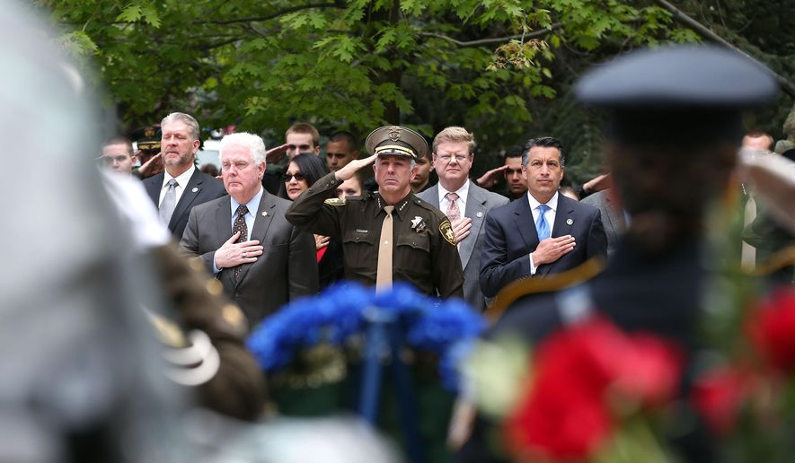 From left, front, Assembly Speaker John Hambrick, R-Las Vegas, Clark County Sheriff Joe Lombardo, Rep. Mark Amodei, R-Nev., and Gov. Brian Sandoval participate in the annual Nevada Law Enforcement Officers Memorial Ceremony on the Capitol Mall in Carson City, Nev., on Thursday, May 7, 2015. The names of Las Vegas Metropolitan Police Officers Alyn Beck and Igor Soldo were added to the memorial after they were killed in the line of duty last June. (AP Photo/Cathleen Allison)