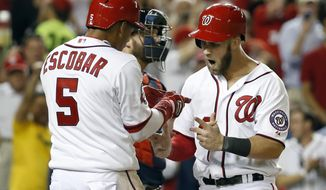 Washington Nationals' Bryce Harper (34) celebrates his three-run homer with Yunel Escobar (5) during the eighth inning of a baseball game against the Atlanta Braves at Nationals Park, Friday, May 8, 2015, in Washington. Harper had two homers in the game. The Nationals won 9-2. (AP Photo/Alex Brandon)
