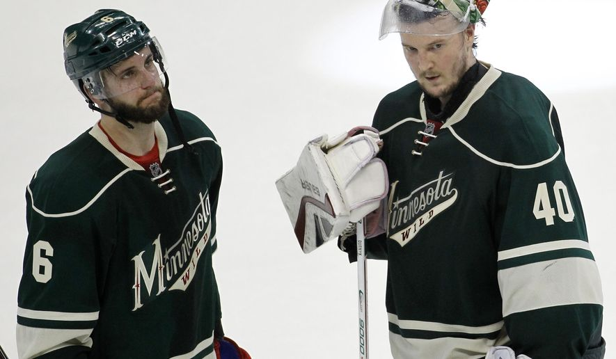 Minnesota Wild defenseman Marco Scandella (6) and goalie Devan Dubnyk (40) react after the Chicago Blackhawks defeated the Wild 4-3 in Game 4 in the second round of the NHL Stanley Cup hockey playoffs, Thursday, May 7, 2015, in St. Paul, Minn. (AP Photo/Ann Heisenfelt)