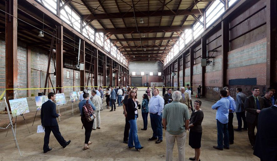 Attendees check out the interior of the former Dillon Supply Company warehouse at 510 W. Martin Street in Raleigh, NC, Friday May, 8, 2015 after a groundbreaking ceremony.  Raleigh Union Station will be home to the new Amtrak station sometime in 2017. The nation's top transportation official says he's more optimistic that high-speed rail will eventually become a reality in the Southeast after Georgia and South Carolina expressed interest in a joint agreement between North Carolina and Virginia to study, coordinate and advocate for the project. (Chuck Liddy/The News & Observer via AP)