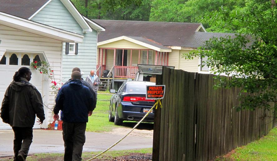 Investigators work at a scene of a shooting in Hollywood, S.C., Thursday, May 7, 2015. A sheriff's deputy responding to a home invasion shot the homeowner in the neck Thursday because he refused to drop his gun, authorities said. (AP Photo/Bruce Smith)
