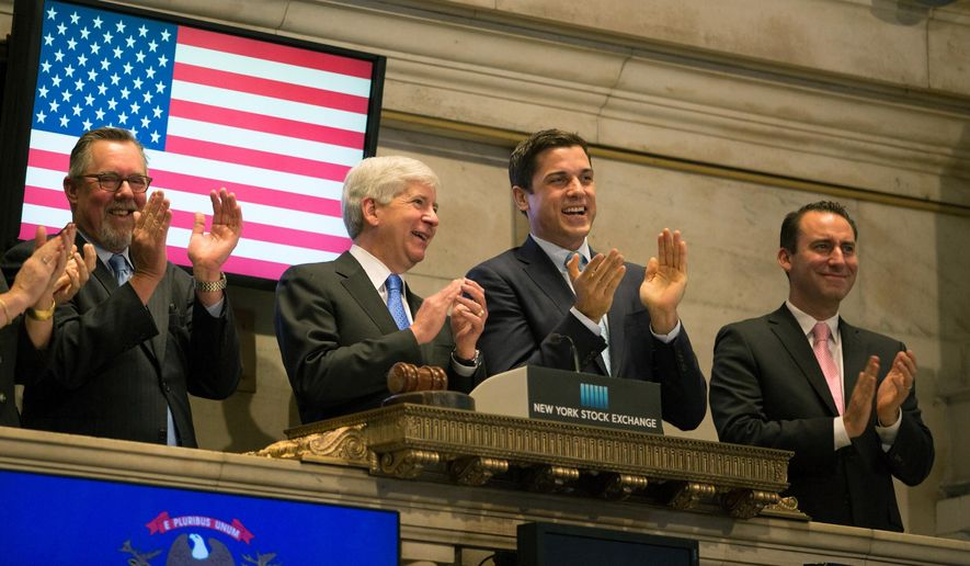 Michigan Gov. Rick Snyder, second left, rings the opening bell at the New York Stock Exchange, Friday, May 8, 2015, in New York. Investors are keeping a close eye on upcoming U.S. jobs figures for signs of growth in the world's largest economy. (AP Photo/Kevin Hagen)