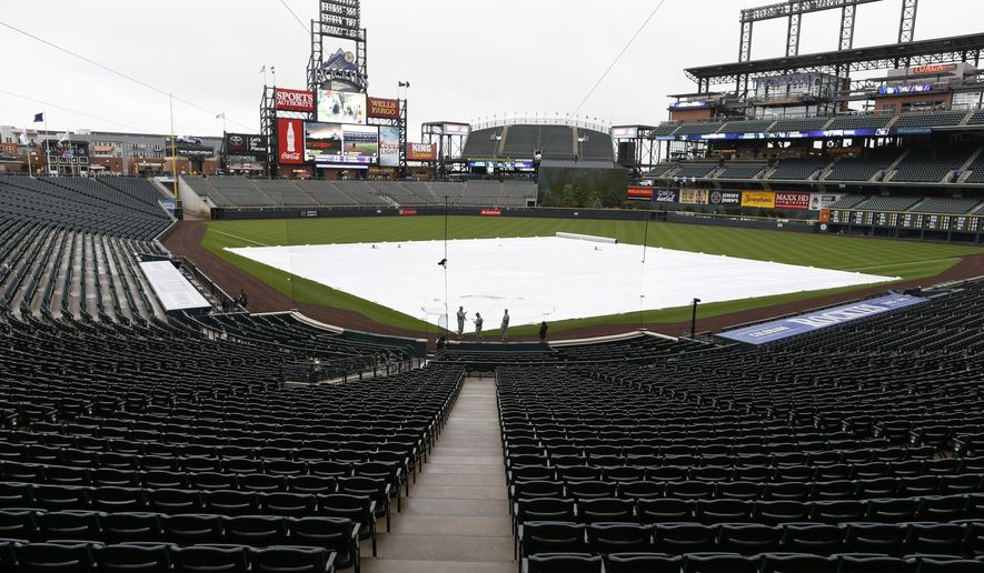 Stands sit empty and the diamond is covered by a tarpaulin in Coors Field after the cancellation of a baseball game between the Los Angeles Dodgers and the Colorado Rockies, Saturday, May 9, 2015, in Denver. Forecasters are predicting three to five inches of snow to fall in the Denver metropolitan area overnight as a spring storm sweeps over the intermountain West. (AP Photo/David Zalubowski)